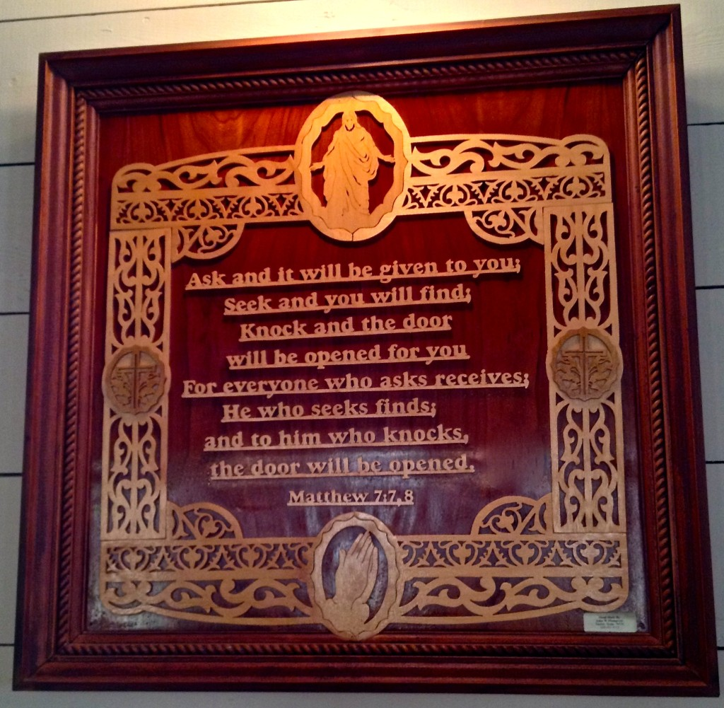 One of the hand-carved, wooden scripture plaques in the sanctuary.