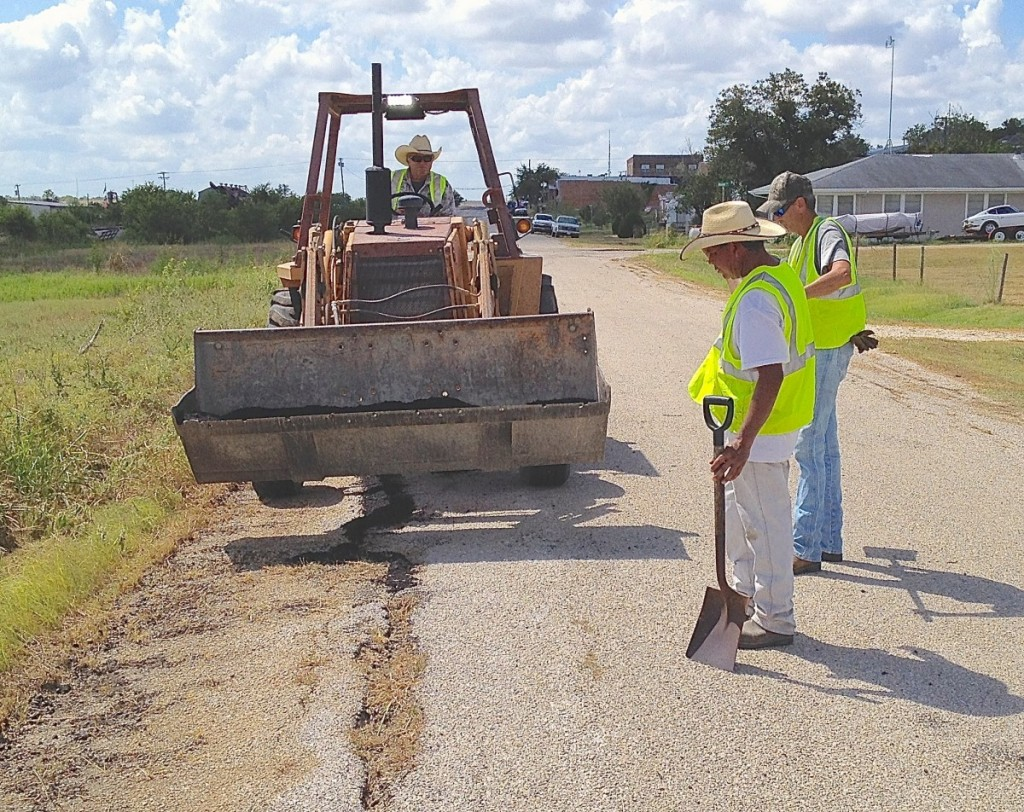 James Naivar uses a front-end loader to prepare the road so his workers can fill in some big cracks.
